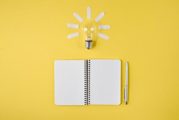 Tampo da mesa do planeamento financeiro com pena, bloco de notas, ampola no fundo amarelo. Foto Premium