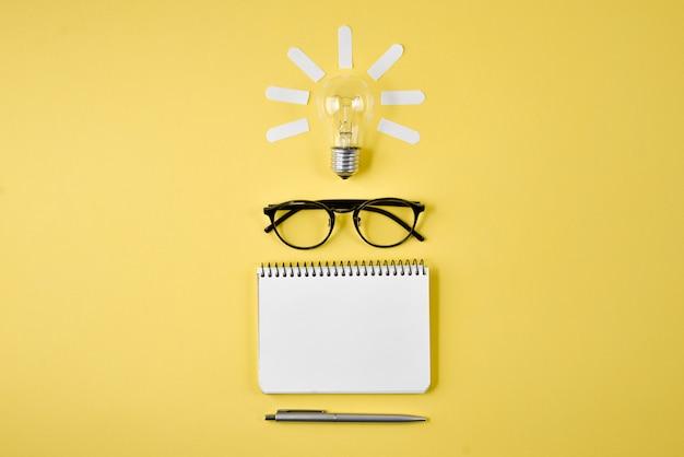 Tampo da mesa do planeamento financeiro com pena, bloco de notas, monóculos e a ampola no fundo amarelo. Foto Premium