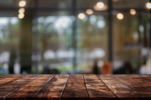 Tampo de madeira vazio no fundo abstrato turva restaurante e café - pode ser usado para exibição ou montagem de seus produtos Foto Premium