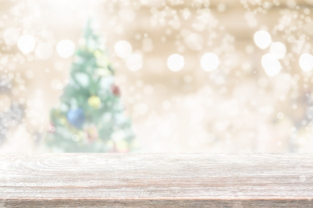 Tampo de mesa de madeira em borrão com fundo de árvore de natal bokeh com queda de neve - pode ser usado para exibir ou montar seus produtos. Foto Premium