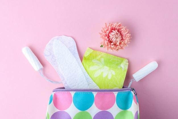 Tampões, absorventes femininos, flores e sacola cosmética para mulheres. cuidados de higiene em dias críticos. ciclo menstrual. cuidando da saúde da mulher. Foto Premium