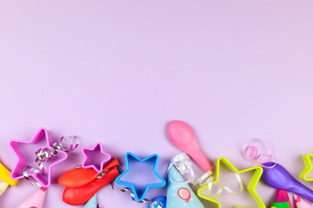 Tampões, balão e estrelas da festa de anos no fundo roxo. fundo colorido da celebração com vários partido. Foto Premium
