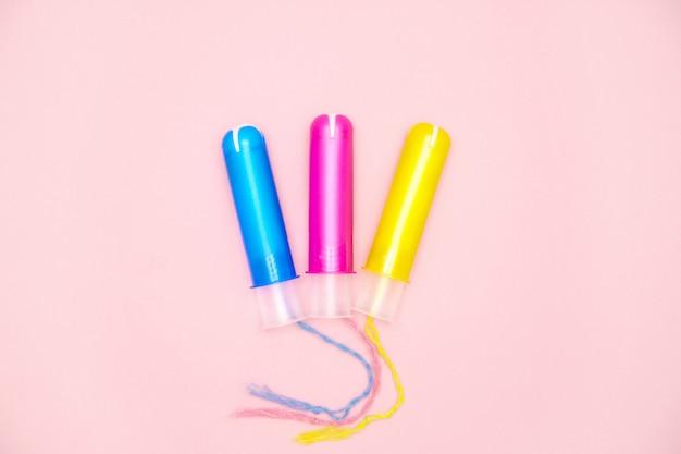 Tampões de algodão do ciclo menstrual três com applicartors amarelos cor-de-rosa azuis no rosa Foto Premium