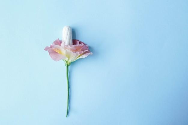 Tampoo branco com flor rosa em fundo azul Foto Premium