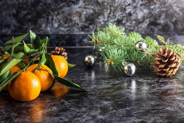 Tangerinas de natal laranja com folhas verdes e abeto em fundo escuro, com espaço de cópia Foto Premium