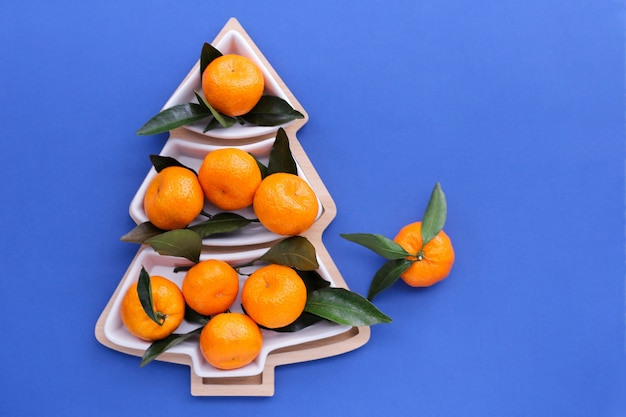 Tangerinas em forma de árvore de natal em um fundo azul. fundo de comida de natal, vista superior. uma divertida árvore de natal comestível Foto Premium