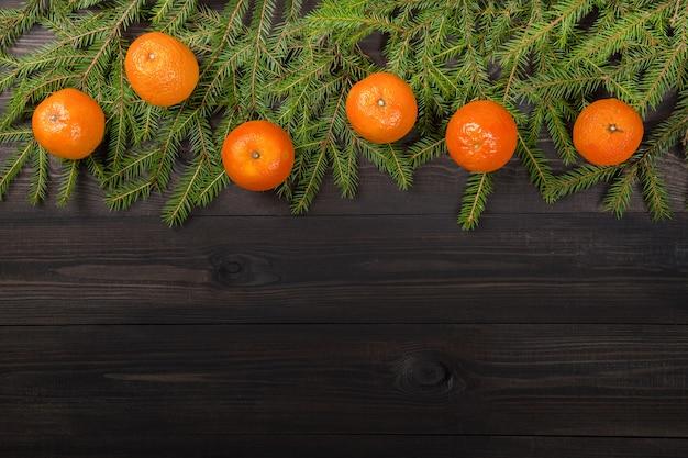 Tangerinas em galhos de árvore do abeto no escuro de madeira Foto Premium