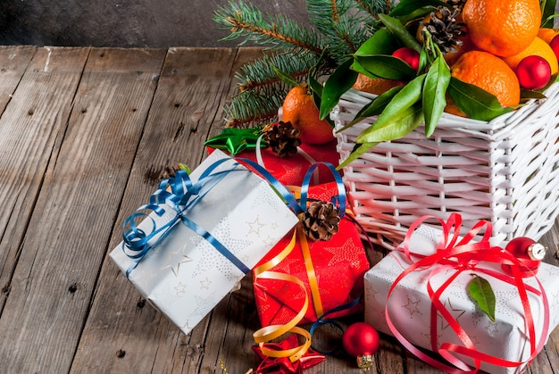 Tangerinas frescas com folhas verdes em uma cesta branca, decoração de natal e caixas de presente Foto Premium