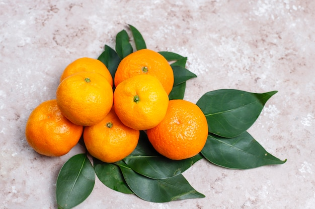 Tangerinas (laranjas, clementinas, frutas cítricas) com folhas verdes na superfície de concreto com espaço de cópia Foto gratuita