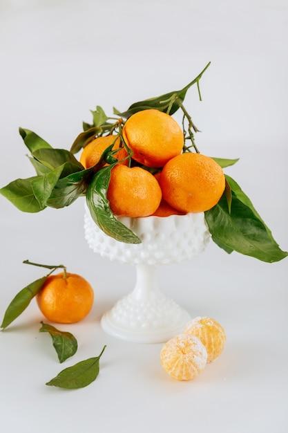 Tangerinas maduras da flórida com folhas verdes em uma tigela branca Foto Premium