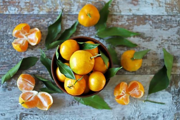 Tangerinas suculentas maduras em uma tigela. folhas de tangerina. mandarinas perfumadas frescas. colher tangerinas. Foto Premium