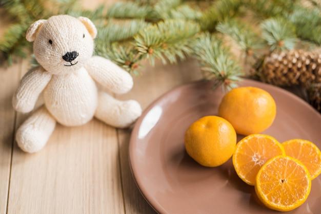 Tangerinas, tangerinas com galhos de árvores de natal com fundo de madeira Foto Premium