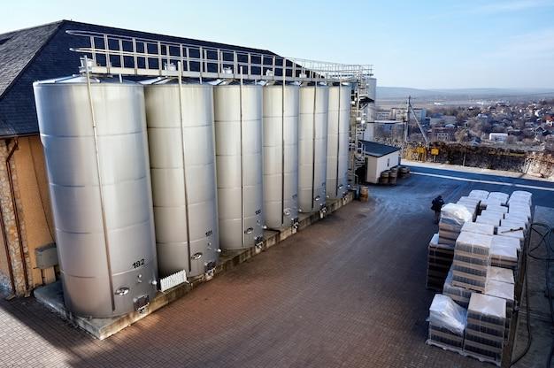 Tanques de armazenamento de vinho de metal com casas de habitação no fundo em uma adega Foto gratuita