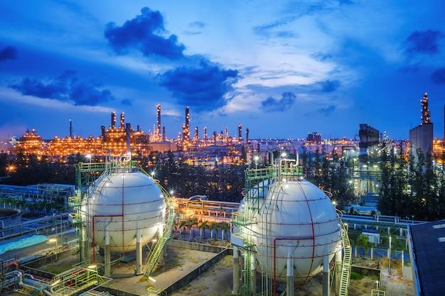 Tanques de esfera de armazenamento de gás e oleoduto na planta industrial de refinaria de petróleo e gás com propriedade de indústria de iluminação de brilho no crepúsculo Foto Premium