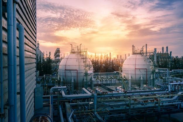 Tanques de esfera de armazenamento de gás e oleoduto na planta industrial petroquímica no fundo por do sol do céu, fabricação de planta da indústria de petróleo Foto Premium