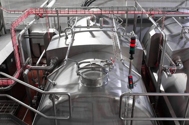 Tanques ou cubas de aço, tubulações e outras ferramentas de equipamentos na oficina da fábrica Foto Premium