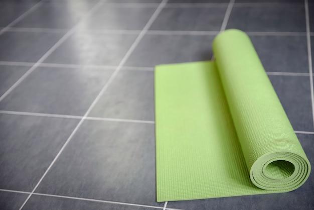 Tapete de yoga verde no chão de ladrilho cinza Foto Premium