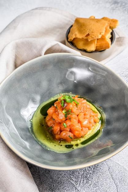 Tartare de salmão com abacate, cebolinha. fundo branco. vista do topo Foto Premium
