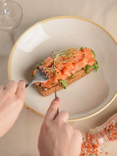 Tartare de salmão com rúcula em um pedaço de pão. em um prato branco Foto Premium