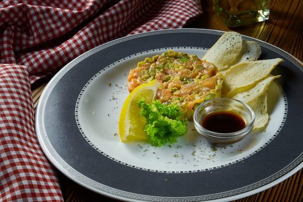 Tartare de salmão fresco, abacate com pão torrado e molho de soja na chapa branca sobre fundo de madeira em composição com pano vermelho. Foto Premium