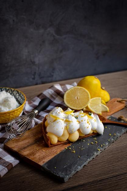 Tarte de limão caseira com limão e merengue, em lenha e panos de cozinha ao lado de limões Foto Premium