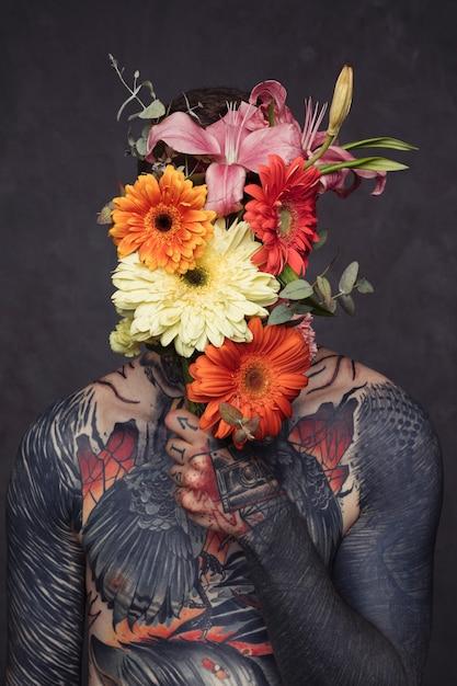 Tatuado, homem jovem, com, perfurado, orelha nariz, segurando, buquê flor, frente, seu, rosto Foto gratuita