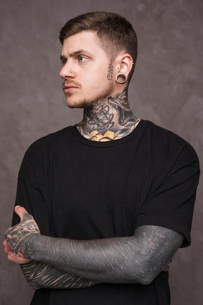 Tatuado jovem com piercing nos ouvidos e nariz com o braço cruzado a desviar o olhar Foto gratuita
