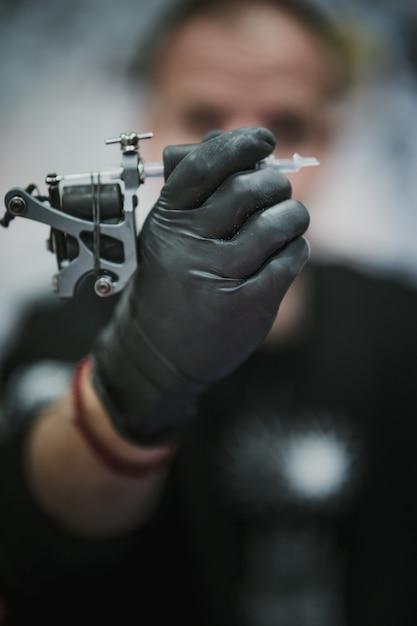 Tatuador segurando e olhando para uma máquina de tatuagem Foto gratuita
