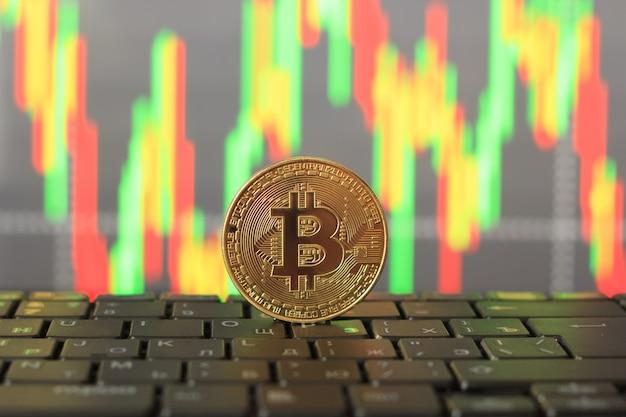 Taxa de bitcoin no gráfico e moeda de ouro, close-up Foto Premium