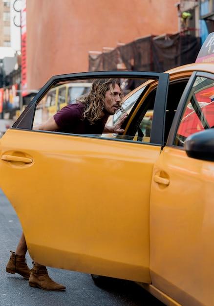 Táxi de equitação jovem na cidade Foto gratuita