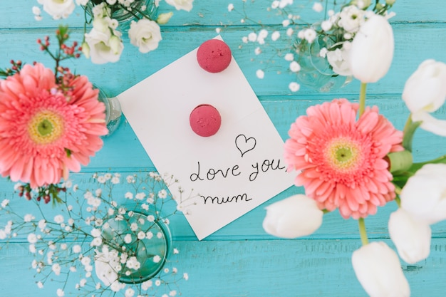 Te amo mãe inscrição com flores e biscoitos Foto gratuita