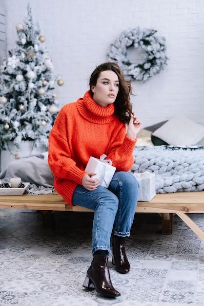 Te desejo um feliz natal! menina com presentes de natal, olhando de lado. sentimento feliz para o ano novo. festa de natal! Foto Premium