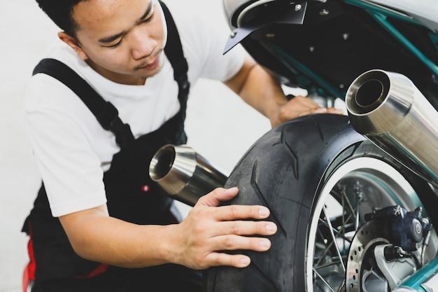 Technican profissional novo que procura o escape do pneu da motocicleta na loja de serviço. Foto Premium