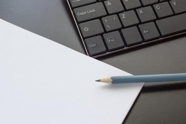 Teclado, caderno e lápis sobre a mesa, vista superior Foto Premium