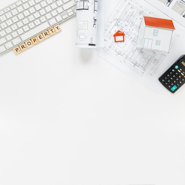 Teclado com modelo de casa e blueprint na mesa de escritório de imóveis Foto gratuita