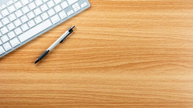 Teclado da pena e de computador no fundo de madeira da mesa. Foto Premium