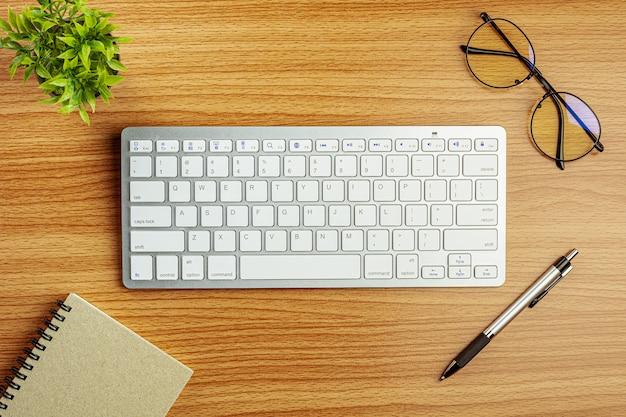 Teclado de computador e papelaria na mesa de madeira Foto Premium