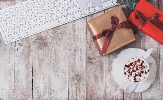 teclado de computador, presente do Natal e copo com marshmallows Foto gratuita