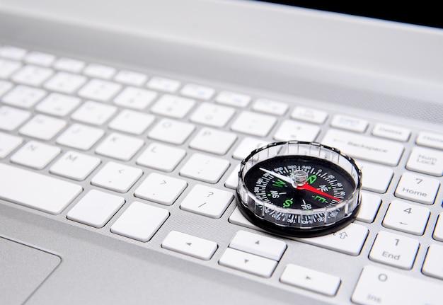 Teclado de notebook e bússola, conceito de navegação na internet. Foto Premium