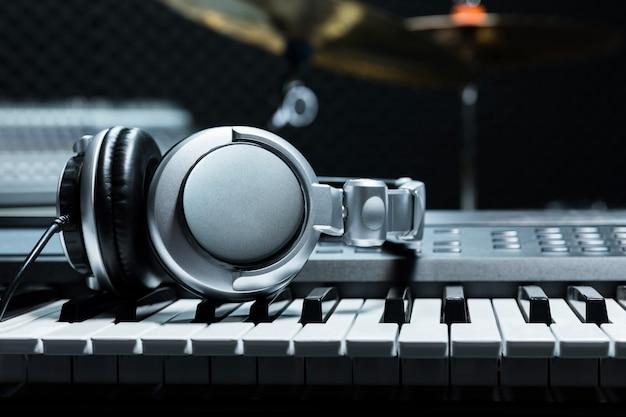 Teclado de piano com fones de ouvido para música, fones de ouvido no teclado de piano, close-up, fones de ouvido no fundo do piano elétrico pelo fundo de instrumentos de música. Foto Premium