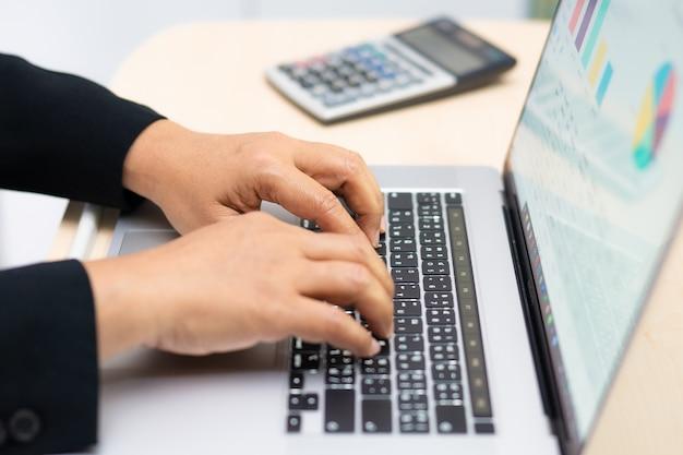 Teclado de tipo asiático contador para inserir informações, trabalhando, calcular e analisar o relatório gráfico gráfico projeto contabilidade com notebook no escritório moderno: finanças e conceito de negócio. Foto Premium