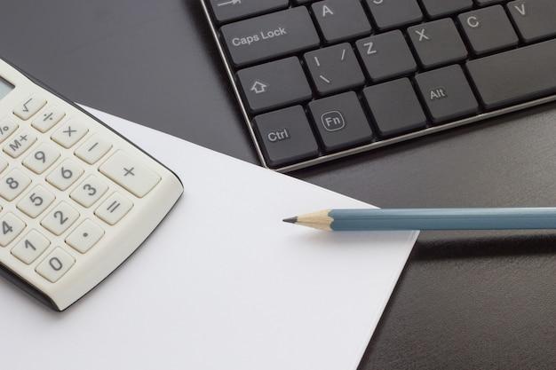 Teclado, notebook e calculadora em cima da mesa, vista superior Foto Premium