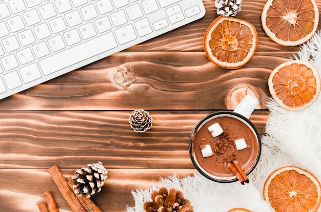 Teclado perto de chocolate quente, laranjas e solavancos de árvore Foto gratuita