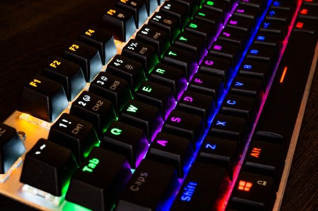 Teclado rgb mecânico de jogos profissionais multicoloridos em cima da mesa Foto Premium