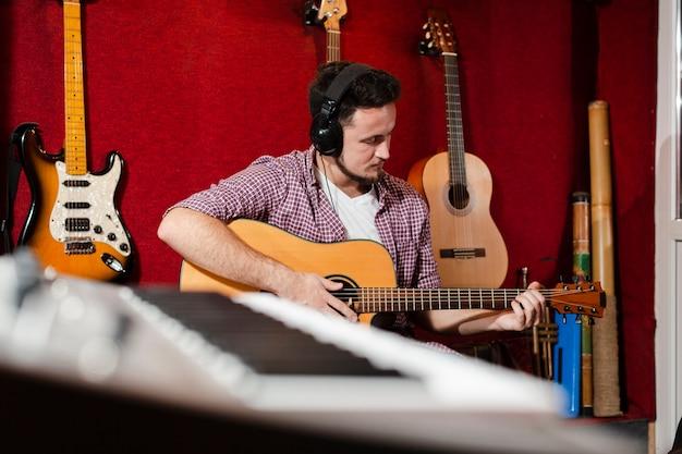 Teclado turva e cara tocando violão Foto gratuita