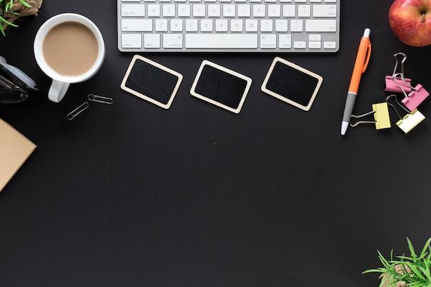 Teclado; xícara de chá; artigos de papelaria da maçã e do escritório no fundo preto Foto gratuita