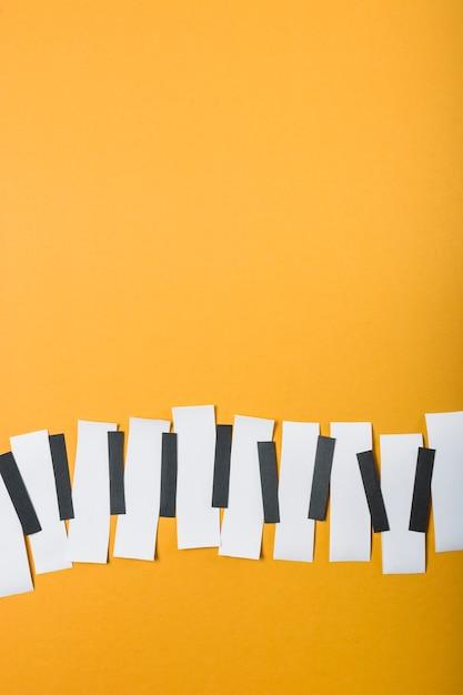 Teclas de piano feitas com papel preto e branco sobre fundo amarelo Foto gratuita