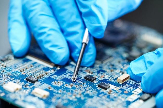 Técnico asiático que repara o computador do prato principal do circuito. Foto Premium