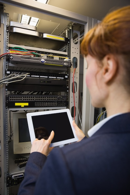 Técnico bonito usando o tablet pc ao reparar o servidor Foto Premium
