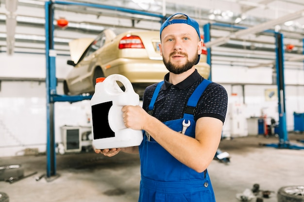 Técnico com oilcan na garagem Foto gratuita